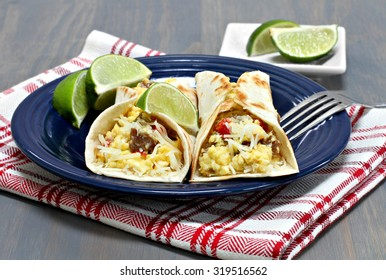 Two egg, sausage, pepper, onion and cheese breakfast tacos.