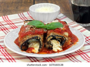 Two eggplant rolletini garnished with fresh basil leaves, a bowl of parmesan and a glass of red wine.  Macro front view.