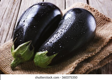 Two eggplants on burlap and wooden table