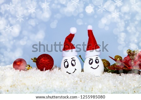 Two eggs in Christmas caps on snow. Card for the New Year and Christmas 79d08674de12