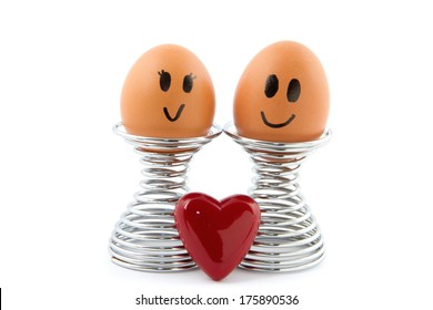 two eggs in egg holder with heart symbol in front of it isolated