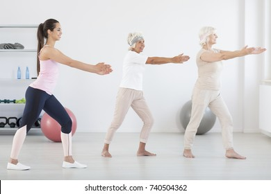 Two elder women exercising at the gym with young personal trainer