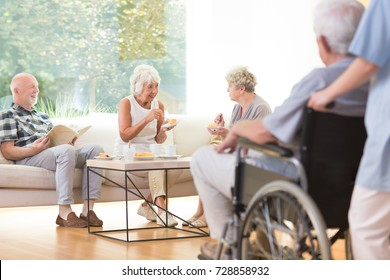 Two elder women sitting on the sofa and eating cake in living room at the rest house for pensioners