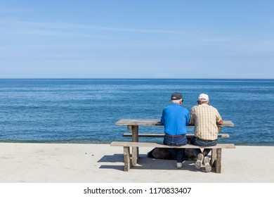 two elderly chatting on a bench