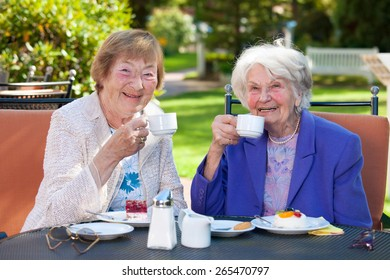 Two Elderly Female Best Friends Sitting at the Outdoor Table While Holding Cups of Coffee and Smiling at the Camera.