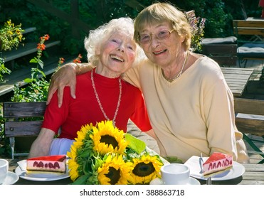 Two elderly ladies enjoying their retirement having tea and cake together at an outdoor restaurant posing arm in arm smiling happily at the camera.