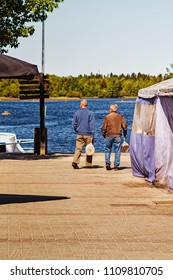 Two elderly men have bought rye bread at the market in Oulu, Finland. The men are admiring the sea on a beautiful summer day.