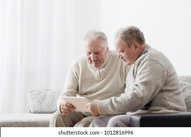 Two elderly men with pc tablet