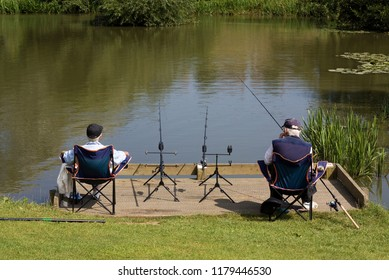 Two elderly men sitting at the edge of a lake fishing.