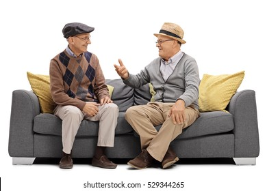 Two elderly men sitting on a sofa and talking isolated on white background