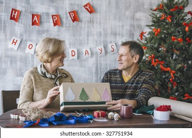 Two elderly people decorating Christmas present with glittering trees and green ribbon