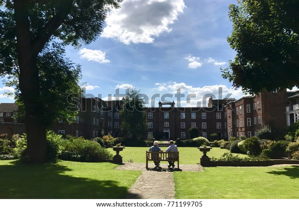 Two elderly people enjoying their retired life in the courtyard of a local residential development in Surbiton, England