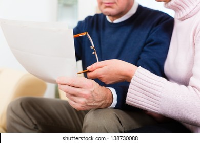 Two elderly people have received a letter, maybe it's a reminder or a Bill