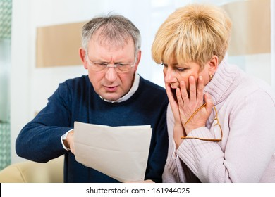 Two elderly people have received a letter, maybe it's a reminder or a Bill, but most likely it is the tax assessment notice