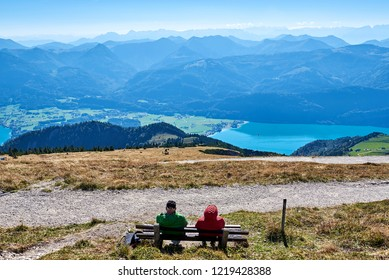 Two elderly people sit on a bench and look at the lake Wolfgangsee. Salzkammergut, region, Alps, Austria.