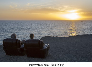 Two elderly people sitting in armchairs by the sea and watching the sunset