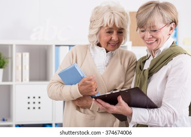 Two elderly students are studying notes from a lecture