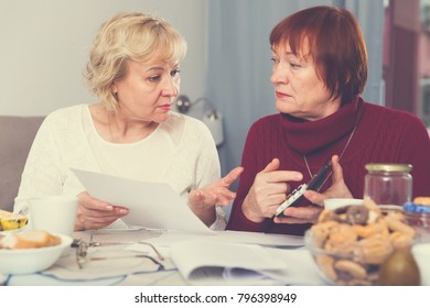 Two elderly women faced financials troubles, sitting at table with bills and calculator