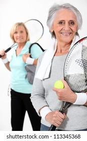 Two elderly women playing tennis