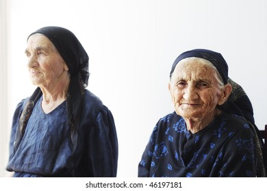 Two elderly women sitting against light wall selective focus