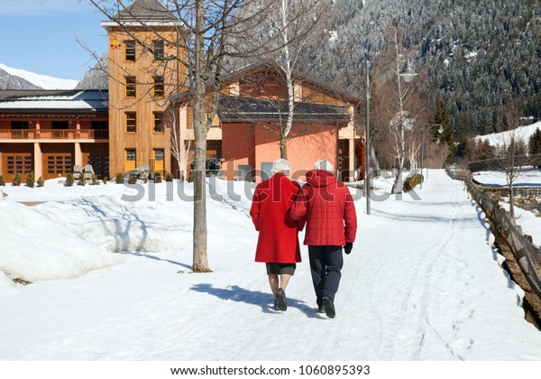 Two eldery persons are walking on snow path in The Alps, Italy