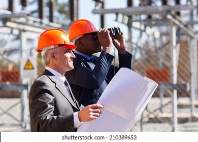 two electrical managers with binoculars visiting power plant