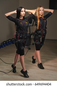 Two Electrical muscular stimulation fitness women in full ems suit doing lunge exercises. Blonde and brunette. Glowing effect. Gothic style.