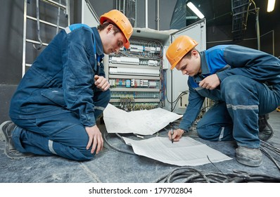 two electrician builder engineer with blue print scheme project in front of fuse switch box