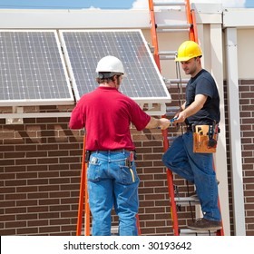 Two electricians installing solar panels on the side of a building.