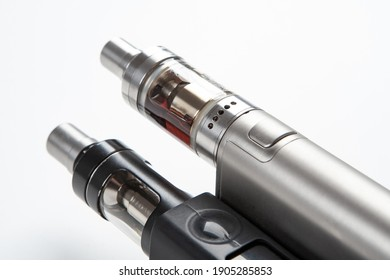 Two Electronic Cigarette close-up. Fragment of Electronic Cigarette on a white background. Vaping cigarettes. Devices for smoking steam. Cigarettes are modern. Concept devices from vape shop