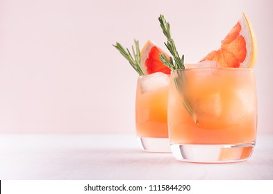 Two elegance cold wet drinking glasses with fresh grapefruit summer cocktail, ice, rosemary on pink background.
