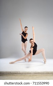 Two elegant ballerinas in black tights. Studio photography.