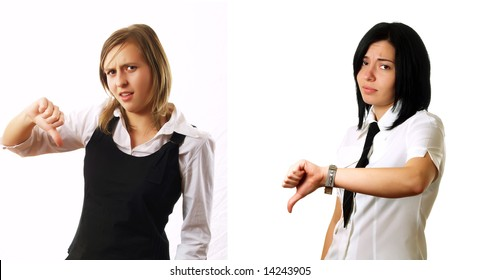 Two elegant businesswomen colleagues are giving the thumbs down and they are sad. They are wearing stylish shirts.