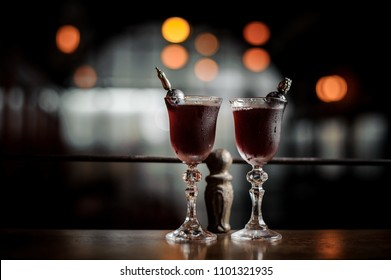 Two elegant glasses filled with fresh sweet and strong summer Arnaud cocktail arranged on the bar counter against dark blurred background