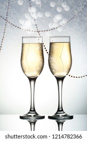 Two elegant glasses with sparkling champagne frost frozen snowflakes Holiday card Christmas, New Year, wedding. Celebration concept with effects of selective focus on bokeh, falling snow, advertising