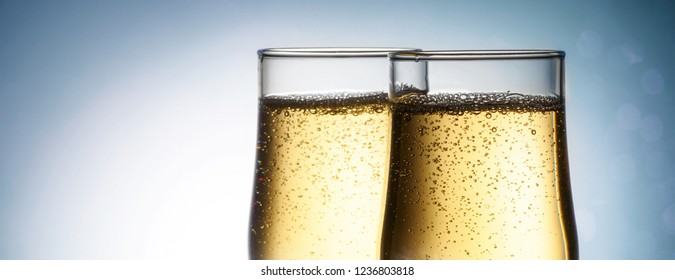 Two elegant glasses with sparkling champagne frost frozen snowflakes Holiday card Christmas, New Year, wedding. Celebration concept with effects of selective focus on bokeh, advertising design
