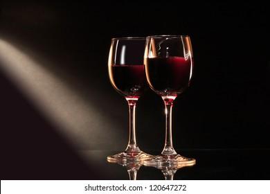Two elegant goblets of red dry wine on dark background