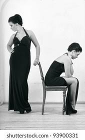 Two elegant ladies in long evening dresses.