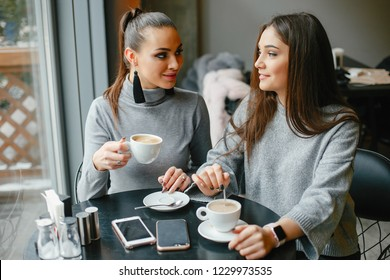 two elegant and magnificent girls sitting in a cafe and drinking a coffee