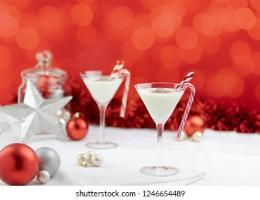 two elegant martini glasses with eggnog, straws and candy canes. Red and white christmas decorations. room for text