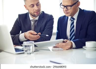 Two elegant men using digital tablet at meeting