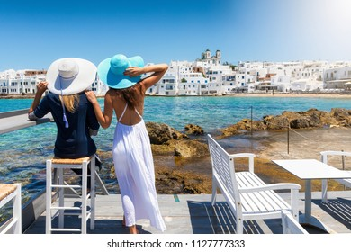Two elegant traveller woman with sun hats enjoy the view to the village of Naousa on the island of Paros, Cyclades, Greece