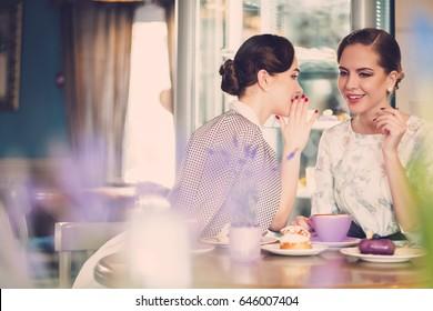 Two elegant young ladies talking secrets in a cafe