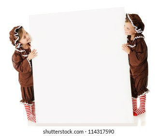 Two elementary gingerbread girls looking across a large white sign (left blank for your text) at each other.  On a white background.