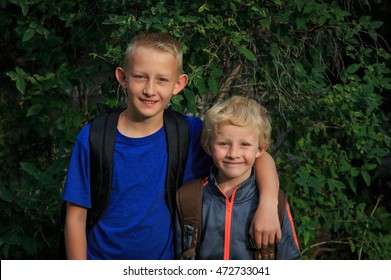 Two elementary school boy students with backpacks ready for school.