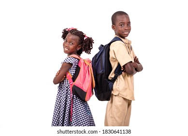 two elementary school students standing on white background back to back with crossed hands and looking at camera smiling.