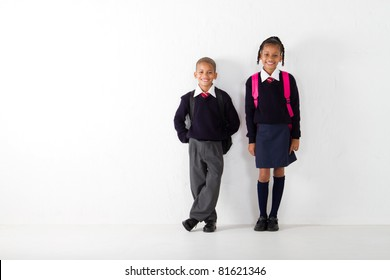 two elementary students standing against wall