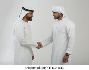 Two emirati men on plain background