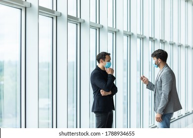 Two employee standing in social distance wearing face mask looking at each other and talking in the office.