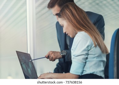 Two employees analyze the schedule of the exchange rates